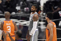 Los Angeles Clippers guard Paul George, center, looks toward referees after being charged with a foul as Phoenix Suns guard Chris Paul, left, and guard Devin Booker stand by during the second half in Game 4 of the NBA basketball Western Conference Finals Saturday, June 26, 2021, in Los Angeles. (AP Photo/Mark J. Terrill)