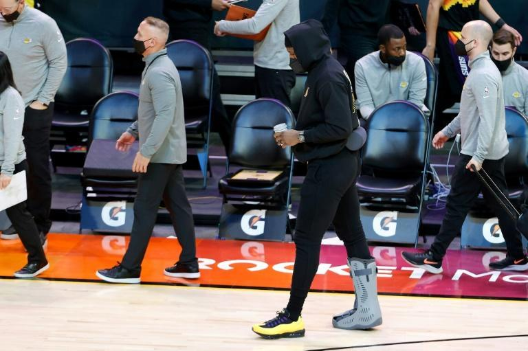 Lakers superstar LeBron James, with a walking boot on his injured right ankle, heads to the locker room from the sideline at halftime of his team's NBA loss to the Phoenix Suns