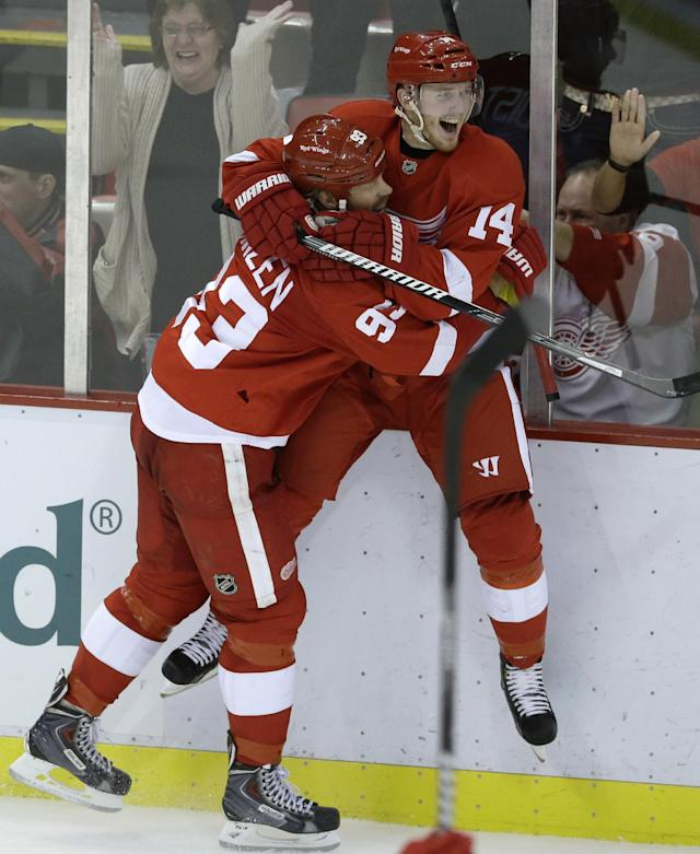 Detroit Red Wings left wing Johan Franzen (93) of Sweden hugs teammate Gustav Nyquist of Sweden after Nyquist's goal during the third period of an NHL hockey game against the Carolina Hurricanes in Detroit, Thursday, Nov. 21, 2013. (AP Photo/Carlos Osorio)