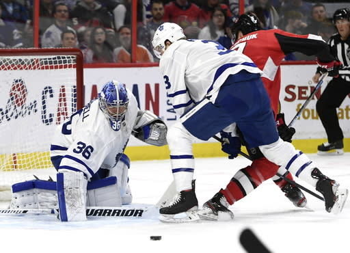 Toronto Maple Leafs goaltender Jack Campbell (36) reaches for the puck as defenseman Justin Holl (3) keeps Ottawa Senators left wing Brady Tkachuk (7) from the puck during first-period NHL hockey game action in Ottawa, Ontario, Saturday, Feb. 15, 2020. (Justin Tang/The Canadian Press via AP)