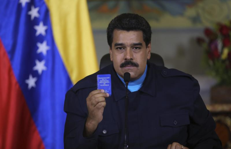 Venezuela's President Nicolas Maduro holds up a book of the country's constitution as he speaks during a national TV broadcast in Caracas in this March 9, 2015 picture provided by Miraflores Palace. The United States on Monday declared Venezuela a national security threat and ordered sanctions against seven officials from the oil-rich country in the worst bilateral diplomatic dispute since socialist Maduro took office in 2013.   REUTERS/Miraflores Palace/Handout via Reuters (VENEZUELA - Tags: POLITICS)  ATTENTION EDITORS - THIS PICTURE WAS PROVIDED BY A THIRD PARTY. REUTERS IS UNABLE TO INDEPENDENTLY VERIFY THE AUTHENTICITY, CONTENT, LOCATION OR DATE OF THIS IMAGE. THIS PICTURE IS DISTRIBUTED EXACTLY AS RECEIVED BY REUTERS, AS A SERVICE TO CLIENTS. FOR EDITORIAL USE ONLY. NOT FOR SALE FOR MARKETING OR ADVERTISING CAMPAIGNS