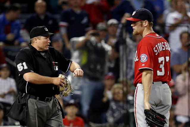 Washington Nationals starting pitcher Stephen Strasburg, right, looks at home plate umpire Marvin Hudson after throwing a wild pitch to Atlanta Braves' Andrelton Simmons in the second inning of a baseball game, Saturday, Aug. 17, 2013, in Atlanta. Strasburg was ejected on the play by Hudson. (AP Photo/David Goldman)