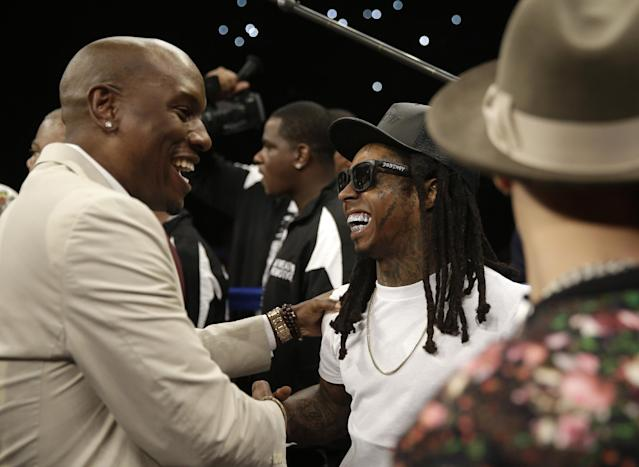 Tyrese, left, greets rapper Lil Wayne before the start of the WBC-WBA welterweight title boxing fight between Floyd Mayweather Jr. and Marcos Maidana Saturday, May 3, 2014, in Las Vegas. (AP Photo/Isaac Brekken)