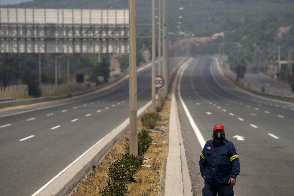 A firefighters walks on the closed highway at during a wildfire in Kapandriti village, about 38 kilometres (23 miles) north of Athens, Greece, Friday, Aug. 6, 2021. Thousands of people fled wildfires burning out of control in Greece and Turkey on Friday, as a protracted heat wave turned forests into tinderboxes and flames threatened populated areas, electricity installations and historic sites. (AP Photo/Thanassis Stavrakis)