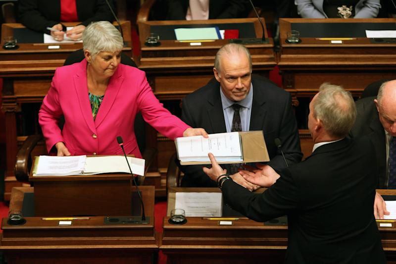 Premier John Horgan looks on as Minister of Finance Carole James passes on a copy of the budget. (Photo: Chad Hipolito/THE CANADIAN PRESS)