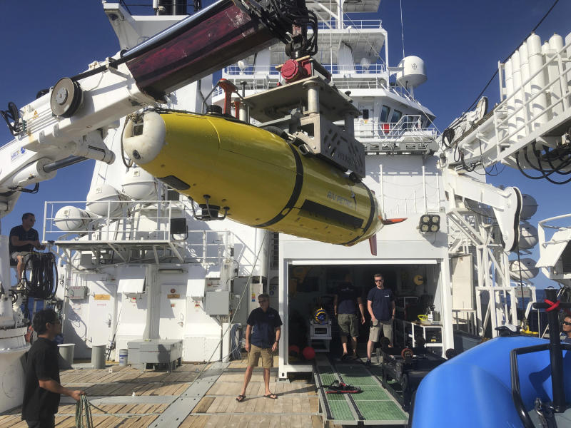 A yellow autonomous underwater vehicle on the back of a larger boat.