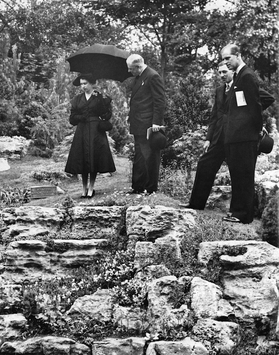Queen Elizabeth II and Prince Philip (far right) admiring the rock garden at the Chelsea Flower Show, London, 20th May 1952. The garden was designed by Winkfield Manor Nurseries of Ascot. (Photo by George W. Hales/Fox Photos/Hulton Archive/Getty Images)