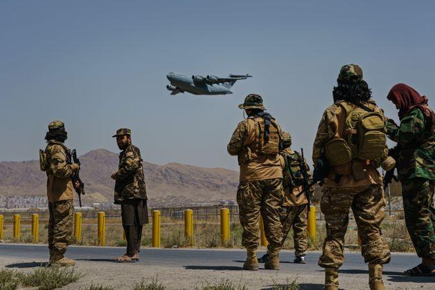 KABUL, AFGHANISTAN -- AUGUST 29, 2021: A C-17 Globemaster takes off as Taliban fighters secure the outer perimeter, alongside the American controlled side of of the Hamid Karzai International Airport in Kabul, Afghanistan, Sunday, Aug. 29, 2021. (MARCUS YAM / LOS ANGELES TIMES) (Photo: Marcus Yam via Getty Images)