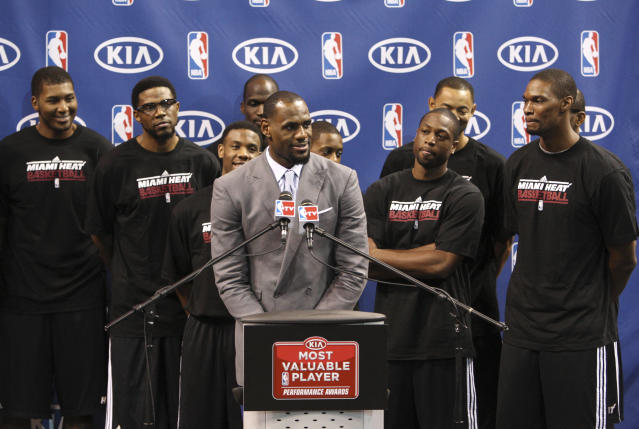 "Surrounded by teammates, Miami Heat's LeBron James speaks after having accepted the NBA MVP trophy, Saturday, May 12, 2012, in Miami. Calling the honor ""overwhelming"" but pointing to a ""bigger goal,"" James on Saturday became the eighth player in NBA history to win the MVP award three times. (AP Photo/Wilfredo Lee)"