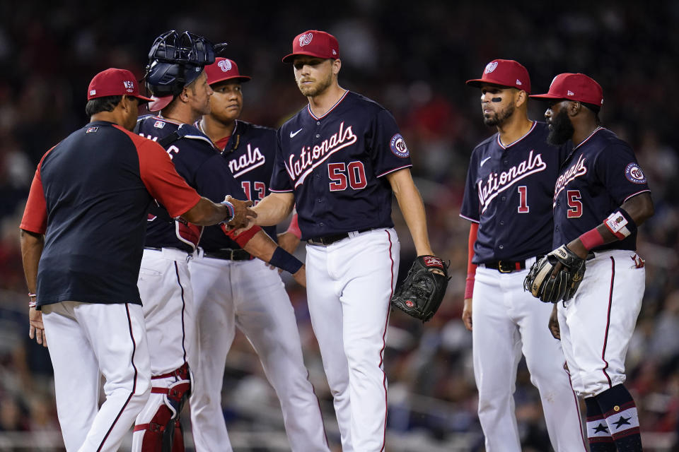 Washington Nationals manager Dave Martinez, left, takes the ball from relief pitcher Austin Voth while going to the bullpen for a reliever against the Los Angeles Dodgers during the seventh inning of a baseball game, Friday, July 2, 2021, in Washington. (AP Photo/Julio Cortez)