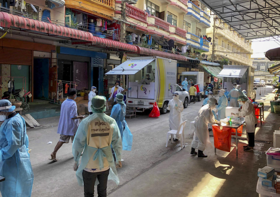 Health workers in protective clothing conduct screening for COVID-19 in Samut Sakhon, south of Bangkok, Thailand, Sunday, Dec. 20, 2020. Thailand reported more than 500 new coronavirus cases on Saturday, the highest daily tally in a country that had largely brought the pandemic under control. (AP Photo/Jerry Harmer)