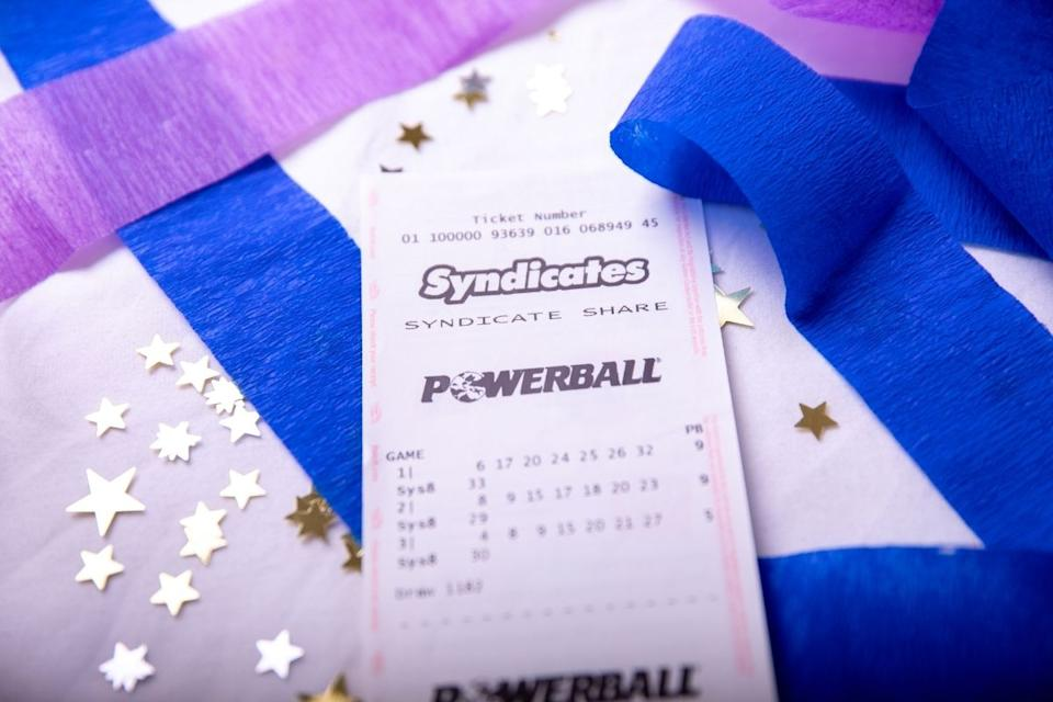Powerball syndicate ticket sits on table with confetti and streamers.