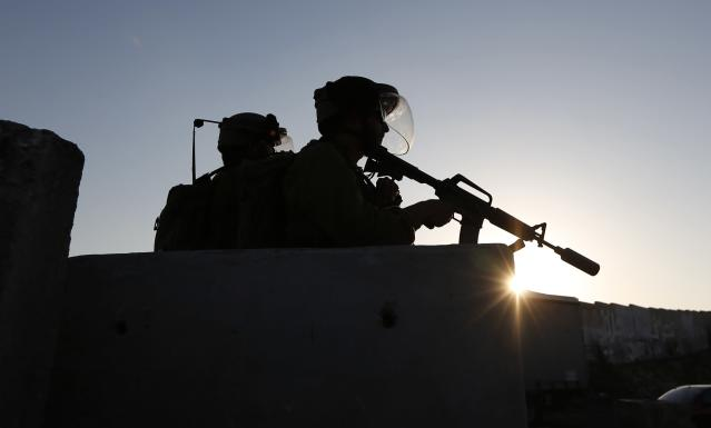 Israeli soldiers keep guard during a protest by Palestinians against the Israeli offensive in Gaza, at Qalandia checkpoint near the West Bank city of Ramallah August 13, 2014. The threat of renewed war in Gaza loomed on Wednesday as the clock ticked toward the end of a three-day ceasefire with no sign of a breakthrough in indirect talks in Cairo between Israel and the Palestinians. REUTERS/Mohamad Torokman (WEST BANK - Tags: POLITICS CIVIL UNREST)