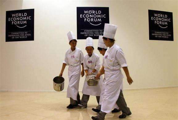 A group of chefs carry a pot of food past signs for the World Economic Forum at the Meijiang Convention Centre in the northern Chinese city of Tianjin September 13, 2010.