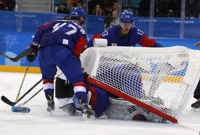 Ice Hockey - Pyeongchang 2018 Winter Olympics - Men's Preliminary Round Match - South Korea v Switzerland - Gangneung Hockey Centre, Gangneung, South Korea - February 17, 2018 - Shin Sang-hoon (L) and Lee Young-jun help out as the net gets dislodged atop goalie Matt Dalton of South Korea. REUTERS/Grigory Dukor