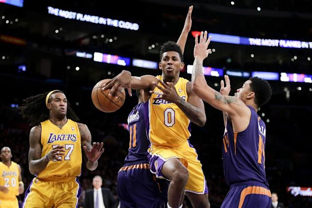 Los Angeles Lakers forward Nick Young, middle, passes to Jordan Hill, left, between Phoenix Suns guard Gerald Green, right, and Markieff Morris during the first half of an NBA basketball game in Los Angeles, Tuesday, Dec. 10, 2013. (AP Photo/Chris Carlson)