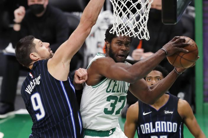 Boston Celtics' Semi Ojeleye (37) tries to shoot against Orlando Magic's Nikola Vucevic (9) during the first half on an NBA basketball game, Sunday, March 21, 2021, in Boston. (AP Photo/Michael Dwyer)