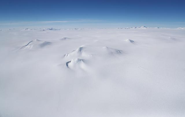 <p>Mountains (center) are mostly covered in ice as in this view from NASA's Operation IceBridge research aircraft, in the Antarctic Peninsula region on Nov. 3, 2017, above Antarctica. (Photo: Mario Tama/Getty Images) </p>