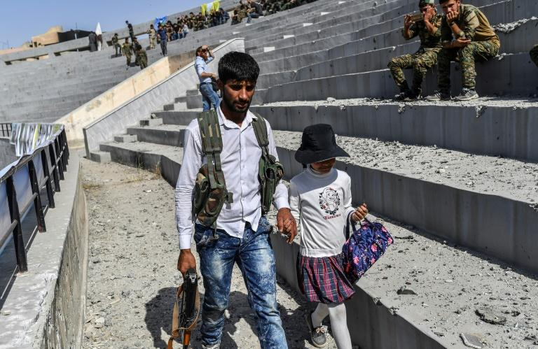 A Syrian fighter walks with his daughter at a stadium in Raqa on October 20, 2017 as they celebrate the city's capture from the Islamic State group