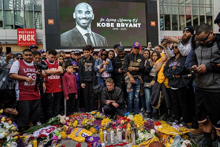 Fans gather in front of a screen with Kobe Bryant's image. On the ground is a memorial with candles, flowers and jerseys.
