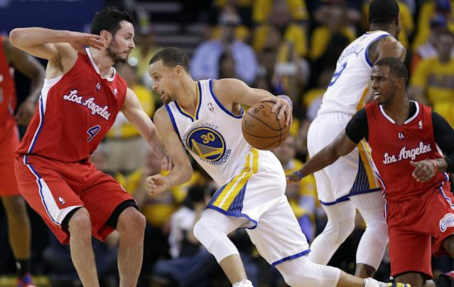 Golden State Warriors shooting guard Stephen Curry (30) drives between Los Angeles Clippers guards J.J. Redick (4) and Chris Paul, right, during the first half of Game 6 of an opening-round NBA basketball playoff series in Oakland, Calif., Thursday, May 1, 2014. (AP Photo/Marcio Jose Sanchez)