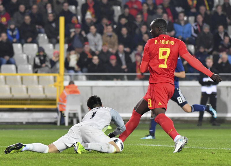 Japan's goalkeeper Eiji Kawashima, left, makes a save on a shot taken by Belgium's Romelu Lukaku during a international friendly soccer match between Belgium and Japan at the Jan Breydel Stadium in Brugge, Belgium, Tuesday, Nov. 14, 2017. (AP Photo/Geert Vanden Wijngaert)