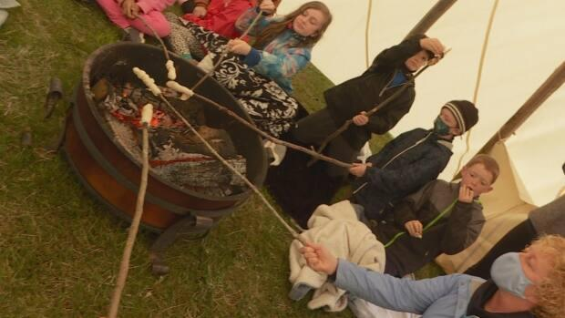 As part of their visit to Lennox Island, students from École Saint-Augustin cooked bannock over an open fire.