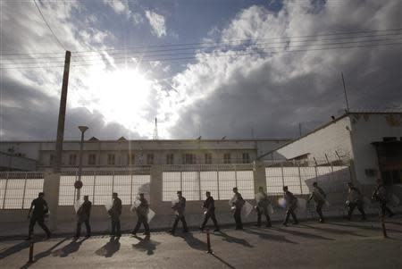 Riot policemen walk outside the Korydallos prison in Athens