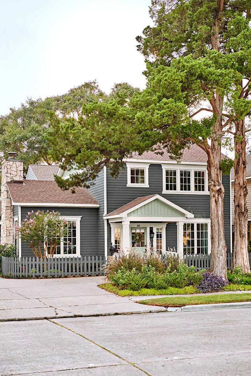 gray farmhouse exterior with white sash windows and a picket fence