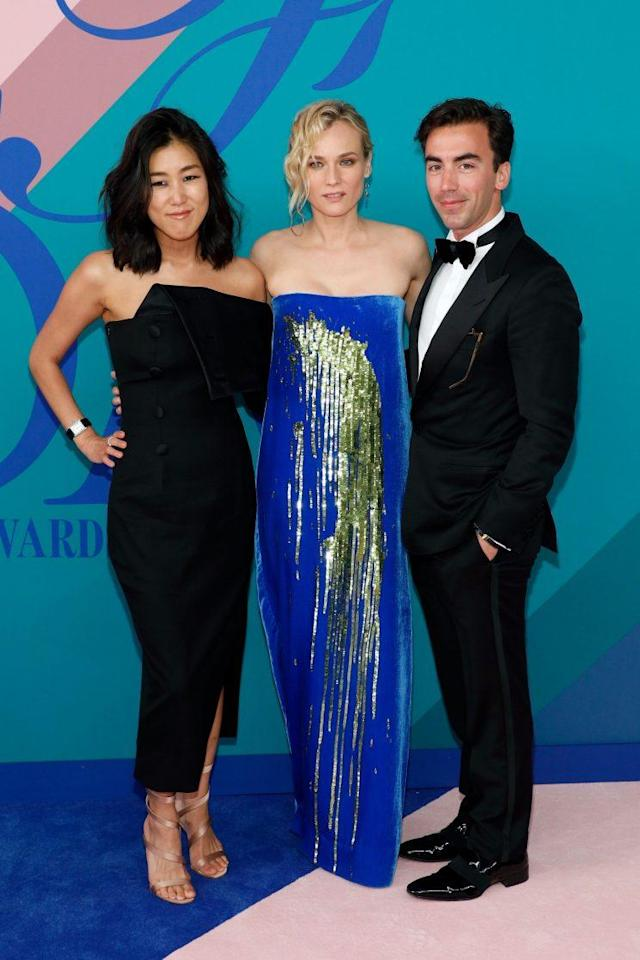 Laura Kim and Fernando Garcia of Monse pose with Diane Kruger wearing one of their designs at the 2017 CFDA awards. (Photo: Getty Images)
