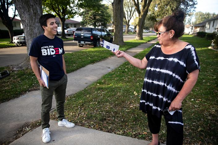 Camilo Haller, a field organizer for Joe Biden's campaign for president, talks to Sandra Armento, of Storm Lake, while knocking doors on Thursday afternoon, Oct. 17, 2019, in Storm Lake.