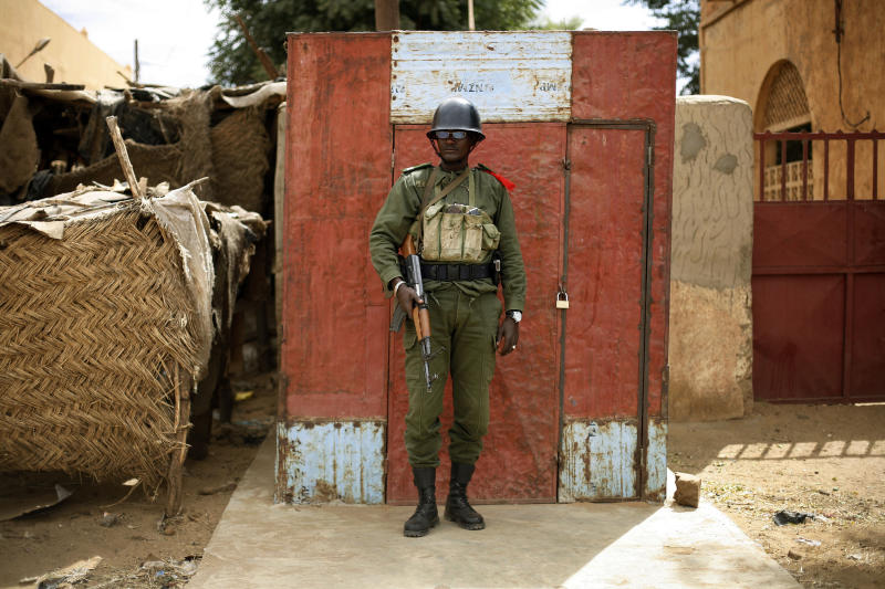 A Malian  soldier stands guard outside the market  in Gao, northern Mali, Tuesday Feb. 12 2013. Soldiers patrol the downtown area in an effort to secure it from Mujao infiltrators, two days after Mujao fighters engaged in a firefight with Malian forces. The attack in Gao shows the Islamic fighters, many of them well armed and with combat experience, are determined and daring and it foreshadows a protracted campaign by France and other nations to restore government control in this vast Saharan nation in northwest Africa.(AP Photo/Jerome Delay)