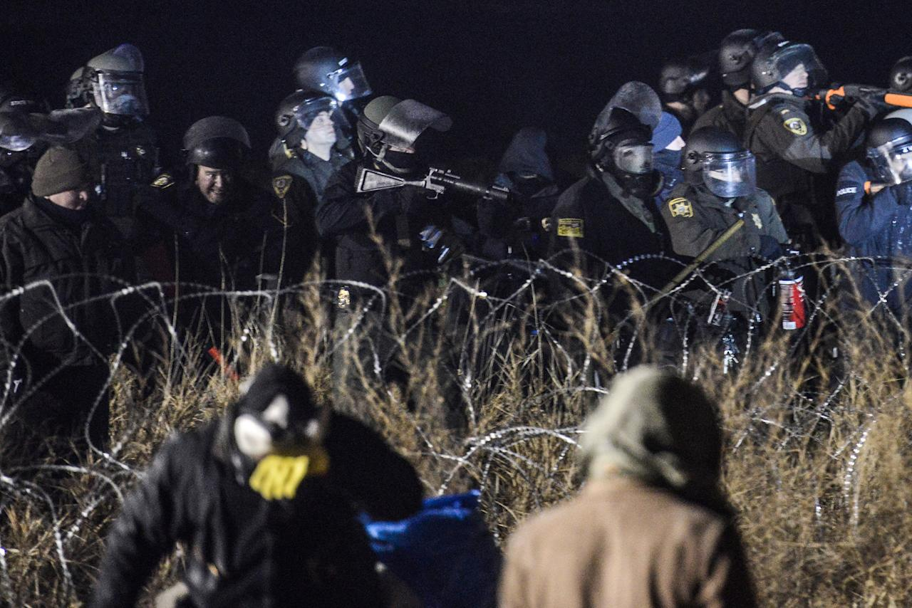 <p>Police confront protesters with a rubber bullet gun during a protest against plans to pass the Dakota Access pipeline near the Standing Rock Indian Reservation, near Cannon Ball, N.D., on Nov. 20, 2016. (Stephanie Keith/Reuters) </p>