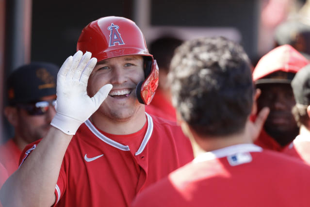 FILE - In this Feb. 25, 2020, file photo, Los Angeles Angels' Mike Trout smiles after scoring during the first inning of a spring training baseball game against the Cincinnati Reds, in Tempe, Ariz. Mike Trout hit two home runs off Zack Greinke and scored four times to help the Los Angeles Angels beat the Houston Astros 9-6 on opening day. Alas, the game was played on a computer, not on the field. But as fans of the Strat-O-Matic board game can attest, make-believe box scores can be fun too. (AP Photo/Darron Cummings, File)
