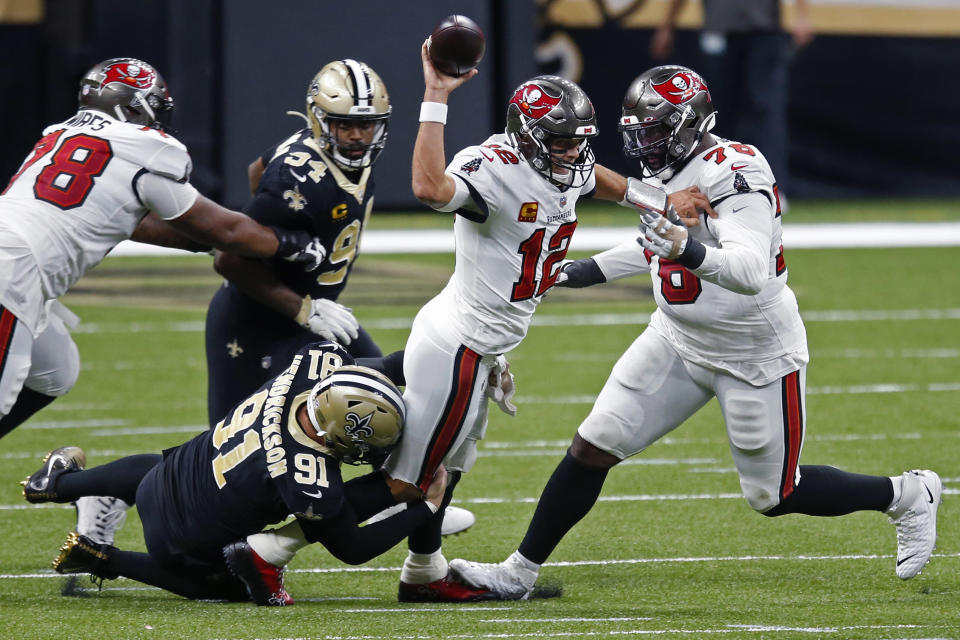 FILE - In this Sunday, Sept. 13, 2020 file photo, Tampa Bay Buccaneers quarterback Tom Brady (12) tries to throw as he is brought down by New Orleans Saints defensive end Trey Hendrickson (91) in the first half of an NFL football game in New Orleans. For all the extraordinary talent the Saints and Buccaneers have at quarterback, running back and receiver, defensive end Cameron Jordan figures that what happens in the trenches will be the decisive factor in their divisional-round playoff clash.(AP Photo/Butch Dill, File)