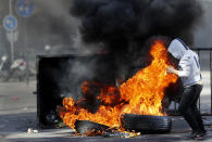 A protester burns tires to block a main road during a protest against the increase in prices of consumer goods and the crash of the local currency, in Beirut, Lebanon, Tuesday, March 16, 2021. Scattered protests broke out on Tuesday in different parts of the country after the Lebanese pound hit a new record low against the dollar on the black market. (AP Photo/Hussein Malla)