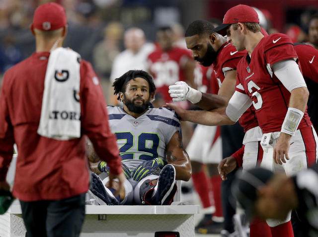 Seahawks defensive back Earl Thomas is greeted by Cardinals players as he leaves the field after breaking his leg during the second half. (AP)