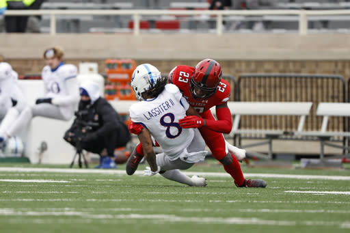 Texas Tech's DaMarcus Fields (23) tackles Kansas' Kwamie Lassiter II (8) during the first half of an NCAA college football game Saturday, Dec. 5, 2020, in Lubbock, Texas. (AP Photo/Brad Tollefson)