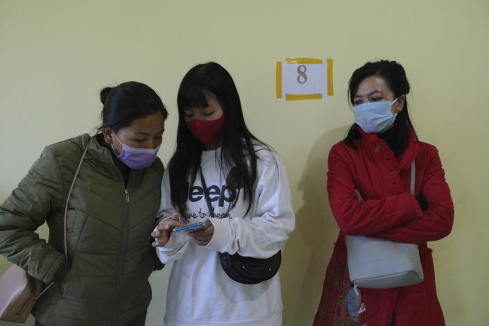 Nurses look at instructions regarding vaccine protocol on a mobile phone after being administered the COVID-19 vaccine at the District Hospital in Ukhrul, in the northeastern Indian state of Manipur, Saturday, Jan. 16, 2021. India started inoculating health workers Saturday in what is likely the world's largest COVID-19 vaccination campaign, joining the ranks of wealthier nations where the effort is already well underway. (AP Photo/Yirmiyan Arthur)