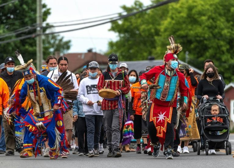 Members of the Mohawk community of Kahnawake, near Montreal, march through the town on Sunday to commemorate the news that a mass grave of 215 indigenous children were found at the Kamloops Residential School in British Columbia, Canada