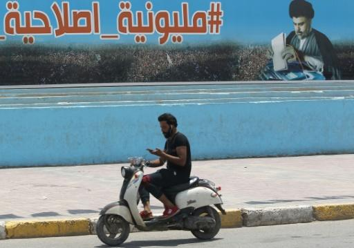 A man rides his scooter past a poster of Shiite cleric Moqtada Sadr in Sadr City, east of the Iraqi capital, on May 14, 2018