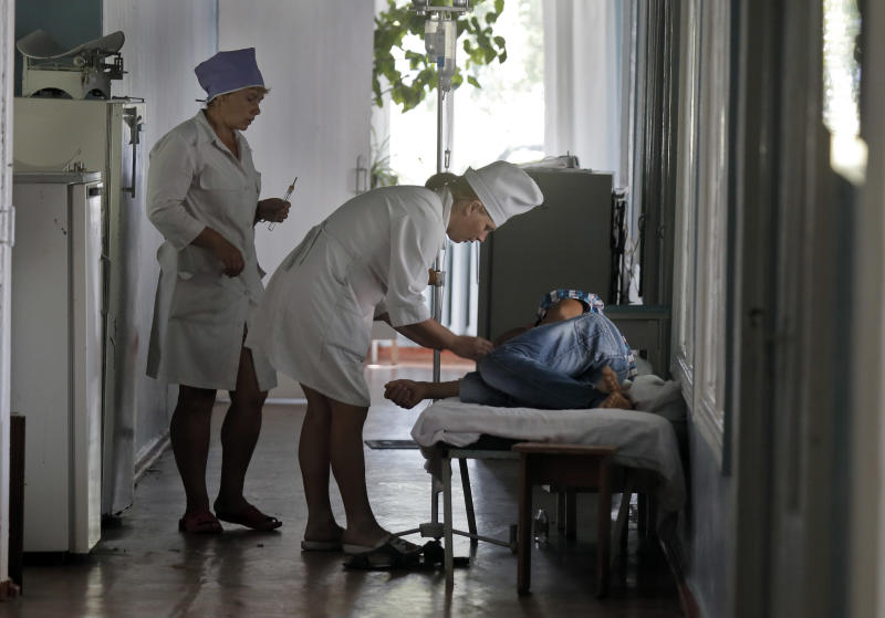 In this photo taken on Tuesday, Aug. 13, 2013, hospital nurses treat a patient after food poisoning in the town of Ruzhyn, Ukraine. Nearly 60 guests, including 14 children, were delivered in an ambulance from a nearby village last week, suffering from food poisoning at a wedding celebrations. They are victims of Ukraine's cult of traditional big wedding hospitality, which calls for treating guests to more food than they can eat and the hosts can safely prepare. (AP Photo/Efrem Lukatsky)