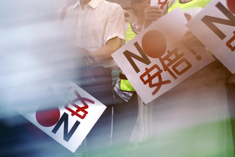 """In this Aug. 8, 2019 photo, protesters with """"No Abe!"""" signs stand during a rally outside Japanese Prime Minister Shinzo Abe's residence in Tokyo. South Korea and Japan have locked themselves in a highly-public dispute over history and trade that in a span of weeks saw their relations sink to a low unseen in decades. (AP Photo/Eugene Hoshiko)"""