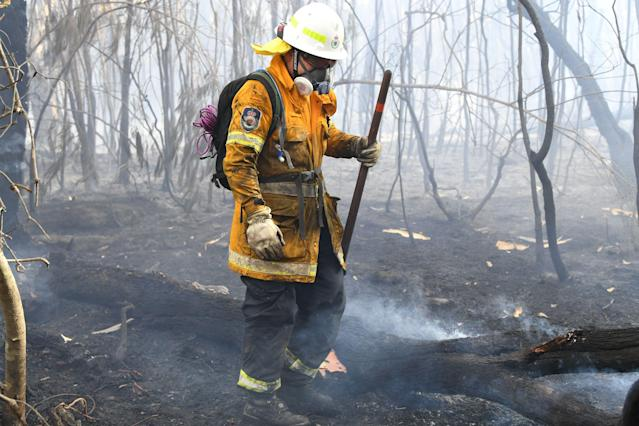 "A firefighter doses a bushfire in the residential area of Sydney on November 12, 2019. - A state of emergency was declared on November 11, 2019 and residents in the Sydney area were warned of ""catastrophic"" fire danger as Australia prepared for a fresh wave of deadly bushfires that have ravaged the drought-stricken east of the country. (Photo by Saeed KHAN / AFP) (Photo by SAEED KHAN/AFP via Getty Images)"
