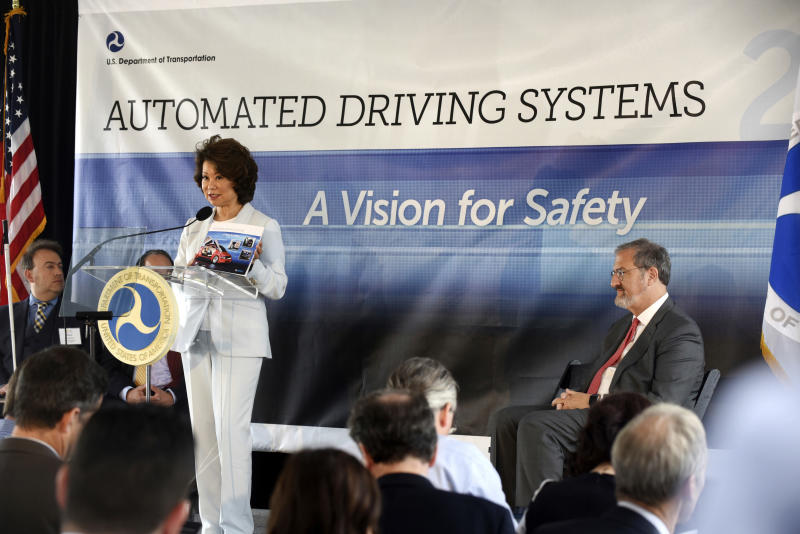 U.S. Transportation Secretary Elaine Chao announces new voluntary safety guidelines for self-driving cars during a visit to an autonomous vehicle testing facility, Tuesday, Sept. 12, 2017, at the University of Michigan, in Ann Arbor, Mich. University of Michigan president Mark Schlissel listens, at right. The new guidelines update policies issued last fall by the Obama administration, which were also largely voluntary. (Max Ortiz/Detroit News via AP)