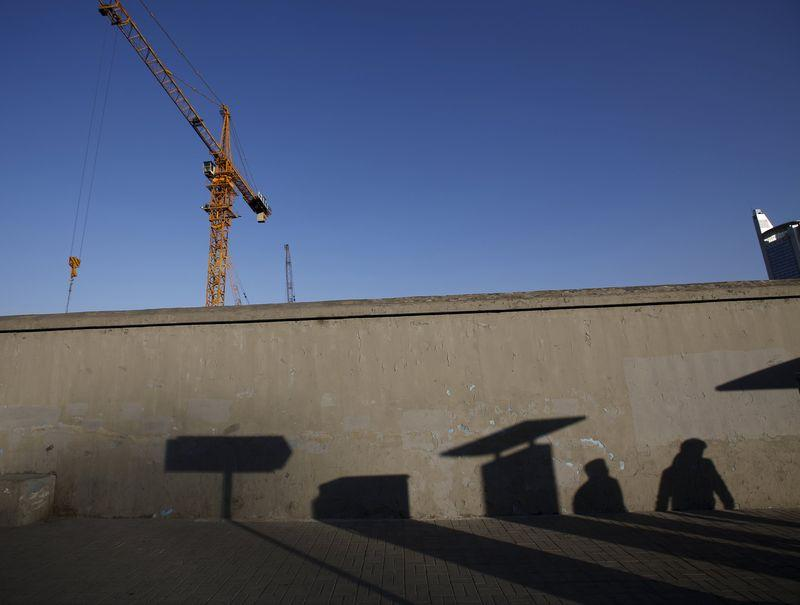 File photo of pedestrians casting their shadows on a wall at a construction site in Beijing