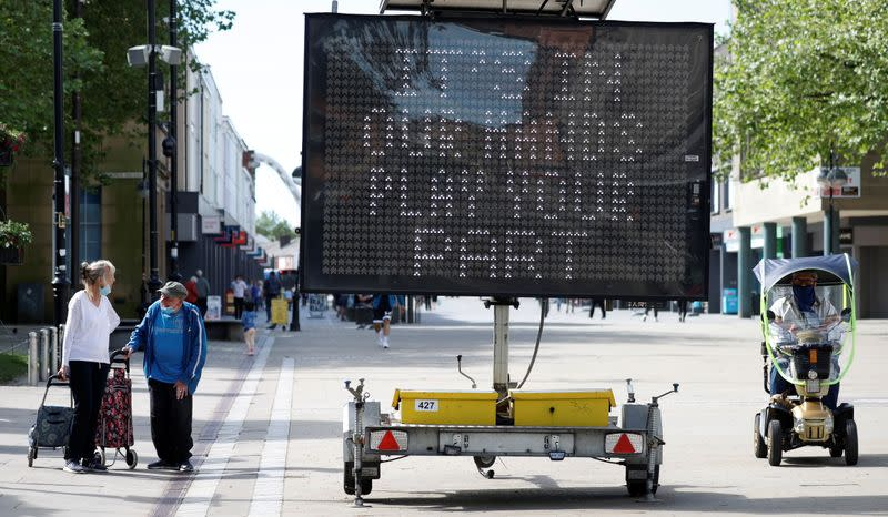 People walk past an information board, amid the COVID-19 outbreak, in Bolton