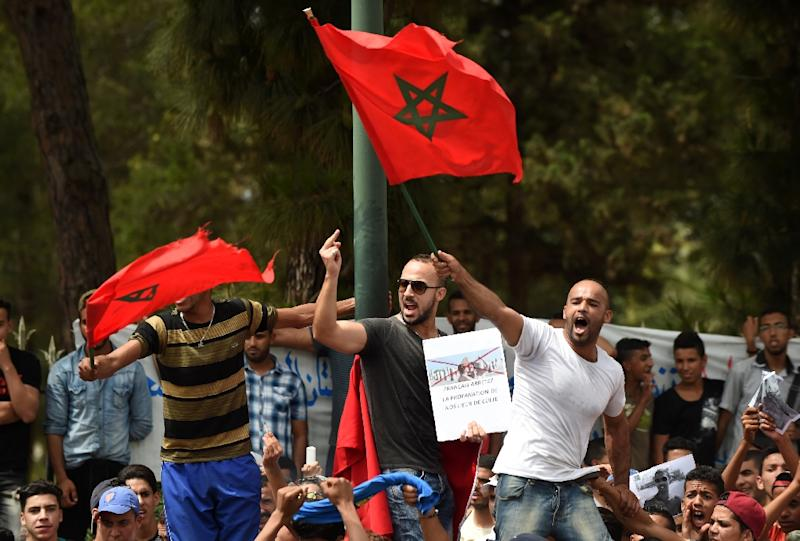 Moroccans wave their national flag in front the French embassy in Rabat, on June 4, 2015, during a demonstration against a topless protest by two members of the controversial feminist campaign group Femen in front of one of the capital's landmarks