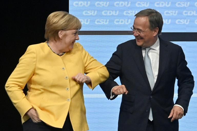 German Chancellor Angela Merkel bumps elbows with would-be successor Armin Laschet at an election rally in Berlin
