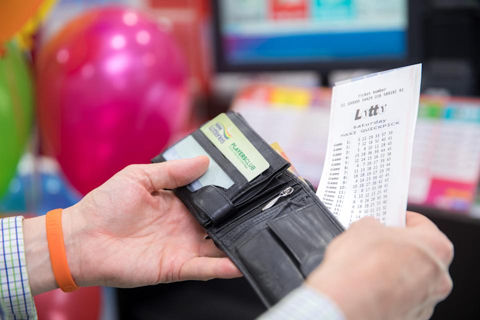 A person pulling a Lotto ticket out of their wallet.